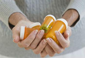 Головная боль при мигрени: женщина держит лекарства